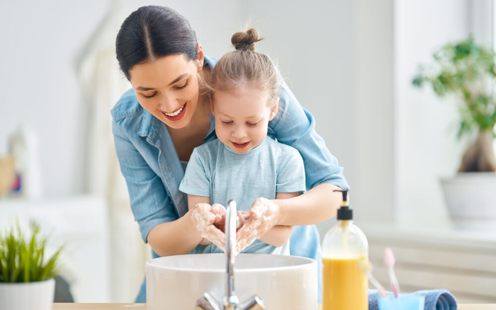 Mom and daughter washing hands in front of bathroom sink