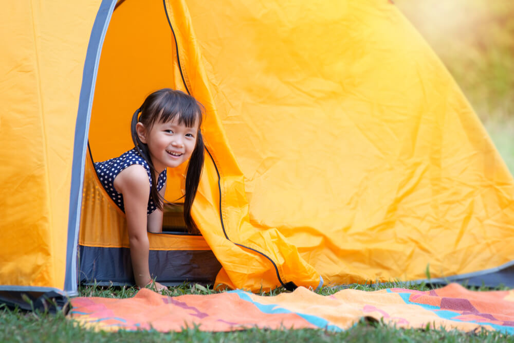 Little girl playing in backyard tent